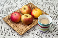 Domestic apples in a wicker basket on embroidered tablecloth and Stock Photos