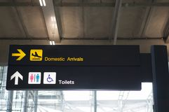 Domestic arrivals and toilets board sign at international airport. Domestic arrivals and toilets information board sign with yellow and white character on black Royalty Free Stock Photo