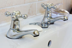 Domestic bathroom taps. Shiny bathroom taps on real bathroom sink with focus on hot water faucet Royalty Free Stock Images