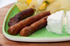 Domestic BBQ sausage with homemade cheese and potatoes Stock Photo