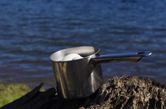Domestic boiled eggs cooling on a lake shore in a camping Royalty Free Stock Photos