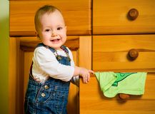 Domestic chores - baby at drawer. Baby opening drawer with clothes on wooden furniture at home Royalty Free Stock Photography