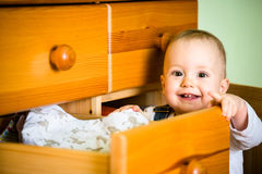 Domestic chores - baby opens drawer. Baby opening drawer with clothes on wooden furniture at home Royalty Free Stock Image