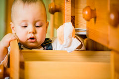 Domestic chores - baby opens drawer royalty free stock photo