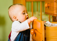 Domestic chores - baby opens drawer. Baby opening drawer with clothes on wooden furniture - home interior Stock Photos
