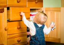 Domestic chores - baby opens drawer. Baby opening drawer with clothes on wooden furniture - home interior Royalty Free Stock Photos