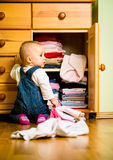 Domestic chores - baby throws out clothes. Baby throws out clothes from wooden furniture at home Royalty Free Stock Photography
