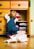 Domestic chores - baby throws out clothes Stock Photos