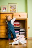 Domestic chores - baby throws out clothes. Baby throws out clothes from wooden furniture at home Royalty Free Stock Photos