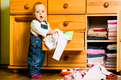 Domestic chores - baby throws out clothes. Baby throws out clothes from wooden furniture at home Stock Photos