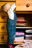 Domestic chores - baby throws out clothes. Baby throws out clothes from wooden furniture at home Royalty Free Stock Images