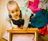 Domestic chores - caught in the act. Baby throws out clothes from wooden furniture at home Royalty Free Stock Images