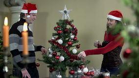 Domestic Christmas tree decorating with red ribbon stock video footage