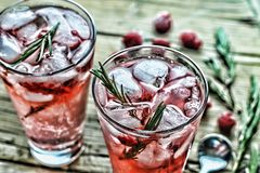 Alcohol cocktail or Fruity cocktail drink decorated with frozen or fresh raspberry, strawberry, rosemary, ice and soda. Domestic c. Domestic cocktail with ice Stock Image