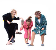 Domestic crush. Three young women in dressing gowns trying to crush something with their slippers royalty free stock images