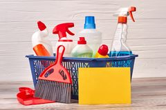 Domestic disinfect products in basket. Assortment of chemicals for house cleaning on wooden background. Tips for speed cleaning stock photos