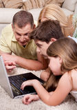 Domestic family of four working with laptop Royalty Free Stock Images