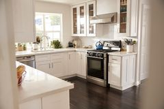 Domestic family kitchen with white furniture and dark wooden floorboards, seen from doorway royalty free stock photography