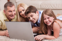 Domestic family lying in living room with lap top Royalty Free Stock Image
