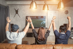 Domestic fans. Three happy young men watching football game. And keeping arms raised while sitting on sofa Stock Images