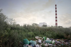 Domestic garbage and factory chimneys Royalty Free Stock Photography