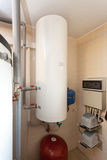 A domestic household boiler room with a new modern solid fuel boiler , heating electric warm water system and pipes. Royalty Free Stock Images