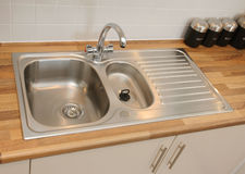 Domestic Kitchen Sink. New modern kitchen sink recessed into wood-effect worktop stock photos