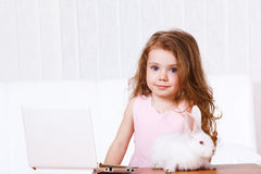 Domestic life. Kid with rabbit beside white laptop Royalty Free Stock Images