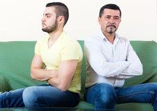 Domestic quarrel between men. Domestic quarrel between father and adult son at the sofa in the living room Stock Photos