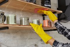 Woman in gloves cleaning furniture with rag at home kitchen. royalty free stock photos