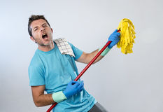 Domestic service man or happy husband cleaning home playing with mop air guitar having fun Stock Images