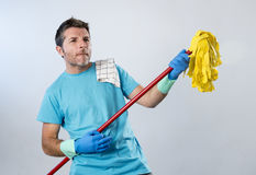 Domestic service man or happy husband cleaning home playing with mop air guitar having fun Royalty Free Stock Photography