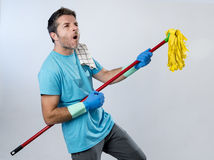 Domestic service man or happy husband cleaning home playing with Stock Image