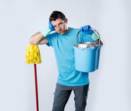 Domestic service man or stressed husband housework washing holdi. Portrait young domestic service cleaner man or stressed husband doing housework washing home Royalty Free Stock Photography