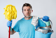 Domestic service man or stressed husband housework washing holding mop and bucket. Portrait young domestic service cleaner man or stressed husband doing Royalty Free Stock Photo