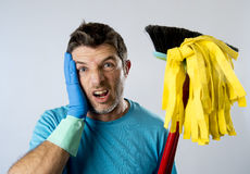 Domestic service man or stressed husband housework washing home with mop and broom. Portrait young domestic service cleaner man or stressed husband doing Royalty Free Stock Photography