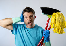 Domestic service man or stressed husband housework washing home with mop and broom. Portrait young domestic service cleaner man or stressed husband doing Royalty Free Stock Image