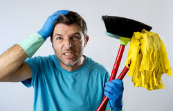 Domestic service man or stressed husband housework washing home with mop and broom. Portrait young domestic service cleaner man or stressed husband doing Royalty Free Stock Photo