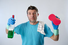 Domestic service man or tired husband angry and stressed house cleaning with spray bottle and sponge Stock Photography