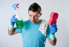 Domestic service man or tired husband angry and stressed house cleaning with spray bottle and sponge Royalty Free Stock Photography