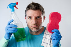 Domestic service man or tired husband angry and stressed house cleaning with spray bottle and sponge Royalty Free Stock Photo
