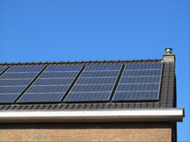 Domestic Solar Panels. New solar panels on the roof of a family home with a background of blue sky Stock Photography