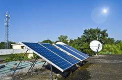 Domestic solar panels. Set of small solar panels on the roof along with dish antenna and mobile phone tower at the background Stock Image