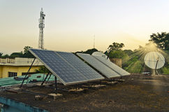 Domestic solar panels. Set of small solar panels on the roof along with dish antenna and mobile phone tower at the background. Chhattisgarh, India Royalty Free Stock Photo