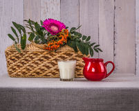 Domestic still life with milk and  branch of mountain ash. Elementary still life with milk jug, basket, flower and  branch  of mountain ash on the rustic Stock Photo