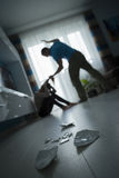 Domestic violence. Man beating the woman on the floor Stock Photos