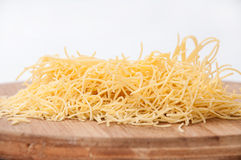 Domestic yellow noodles on a kitchen board Royalty Free Stock Photo