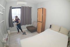 Domestica asiatica Cleaning Service con il pavimento di pulizia di zazzera su una camera da letto immagine stock libera da diritti
