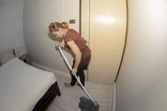 Domestica asiatica Cleaning Service con il pavimento di pulizia di zazzera su una camera da letto immagini stock libere da diritti
