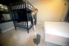 Domestica asiatica Cleaning Service con il pavimento di pulizia di zazzera su una camera da letto Fotografia Stock